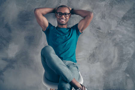 Close up photo amazing he him his dark skin macho sit cozy chair hold arms hands behind head pause break daily nap excited glad wear specs casual blue t-shirt sneakers pants modern room office indoors