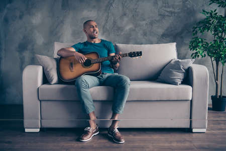 Full length body size photo amazing he him his dark skin macho hold arms hands guitar vocal soloist playing alone rock legends hits wear blue t-shirt pants sit comfy divan room office house indoors