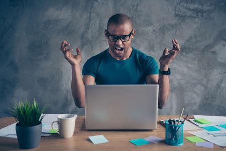 Foto de cerca enojo increíble él él su macho apuesto cuaderno mesa planta verde persona confiable difícil no puede hacer deber tarea usar especificaciones pantalones camiseta azul sentarse silla en el interior estación de trabajo oficina Foto de archivo
