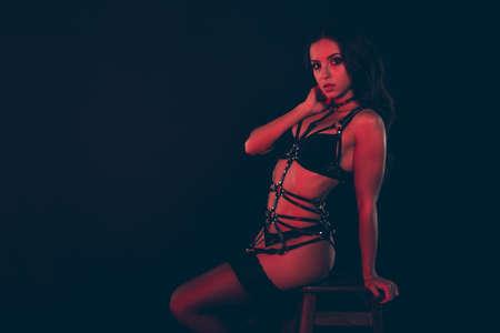 Porträt einer netten, süßen, coolen, süßen, liebenswerten, anmutigen, weiblichen, attraktiven, dünn geschnittenen, schlanken, sportlichen, gewellten Dame, die auf einem Stuhl sitzt rotes Licht einzeln auf dunklem schwarzem Hintergrund posiert Standard-Bild