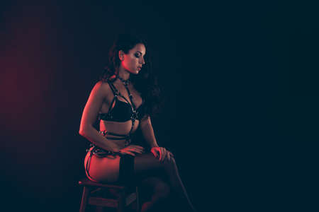 Profile side  of nice lovely winsome magnificent delicate attractive wavy-haired lady wearing swordbelt sitting on chair isolated over red light black background Stock Photo