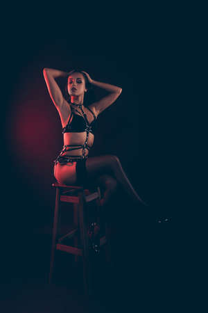 Vertikal von schöner, prächtiger, attraktiver sportlicher Passform, dünner, gewellter Dame mit Schwertgürtel, die auf einem Barhocker sitzt und das Fixierhaar einzeln auf rotem, schwarzem Hintergrund berührt Standard-Bild