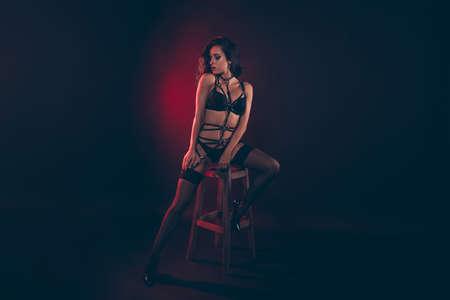 Retrato de tamaño de cuerpo entero de agradable atractivo deportivo en forma delgada perfecta dama de cabello ondulado con cinturón de espada sentado en el taburete de la barra disfrutando del estilo de vida aislado sobre fondo negro rojo claro