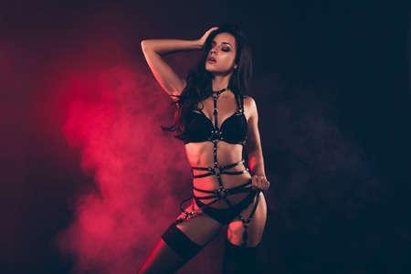Porträt einer netten, liebenswerten, atemberaubenden, bezaubernden, attraktiven, sportlichen, gewellten Dame, die einen Schwertgürtel trägt und streichelndes, berührendes Haar einzeln auf schwarzem, rotem Lichthintergrund posiert