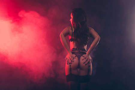 Rear back behind view of attractive stunning sportive perfect muscular fit thin shape form line wavy-haired lady wearing swordbelt teasing holding in hands bum isolated on red light black background Stock Photo