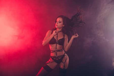 Schöne verträumte attraktive prächtige faszinierende charmante sportliche perfekte Figur gewellte Dame mit Schwertgürtel neckt posiert mit geschlossenen Augen und genießt das Leben einzeln auf rotem, schwarzem Hintergrund