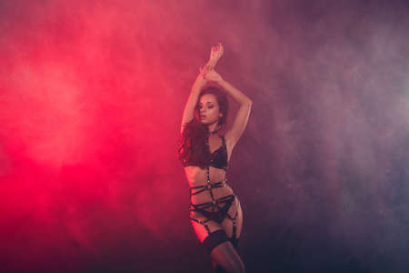 Nice attractive fascinating charming sportive perfect figure wavy-haired lady wearing swordbelt teasing posing closed eyes enjoying lifestyle night club clubber isolated on red light black background