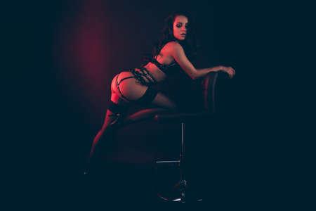 Profilseitenansicht-Porträt einer schönen, bezaubernden, attraktiven, perfekten sportlichen Form in Form einer gewellten Dame, die einen Schwertgürtel trägt und sich auf einen Bürostuhl stützt und isoliert über rotem, schwarzem Hintergrund genießt
