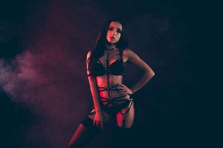 Porträt einer schönen, coolen, bezaubernden, attraktiven, sportlichen, perfekt dünnen Passform, einer wellenförmigen Dame mit Schwertgürtel, die das Leben genießt, isoliert auf schwarzem, rotem Licht
