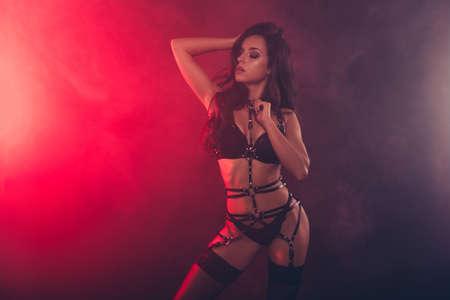 Schöne stilvolle trendige attraktive atemberaubende liebenswürdige sportliche muskulöse Form wellenförmige Dame mit Schwertgürtel necken posiert geschlossene Augen einzeln auf rotem hellschwarzem Hintergrund