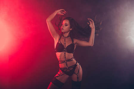 Nice attractive stunning fascinating charming winsome sportive muscular perfect wavy-haired lady wearing swordbelt teasing posing closed eyes isolated on red light black background