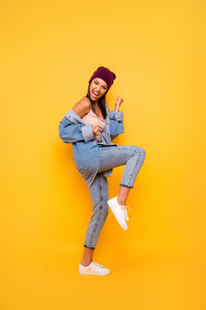 Full length body size view photo of charming content lady feel rejoice excited have luck lucky lottery fan raise fists hands scream shout yeah dressed denim clothing cap isolated on vivid background