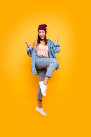 Full length body size view photo cute pretty attractive youth millennial rejoice satisfied lottery aim celebration luck lucky cap scream shout yeah raise fists isolated yellow background denim costume Banco de Imagens