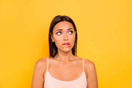 Close up photo beautiful she her lady look empty space fear hide eyes bite lip bad wrong unsuitable situation feel guilty wear casual pastel tank-top outfit clothes isolated yellow bright background Stock Photo