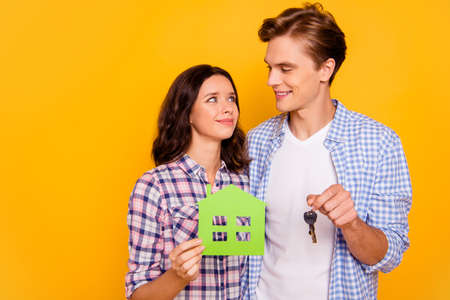 Close up photo of pair in love he him his she her lady boy gladly looking to eyes hands holding accessories from new apartments wear casual plaid shirts outfit isolated on yellow background