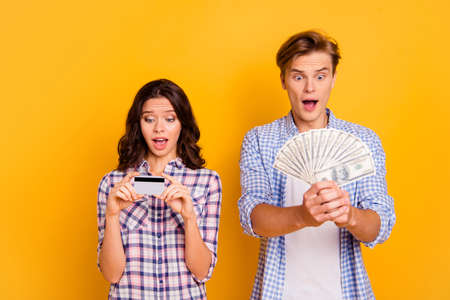 Close up photo of pair fan of bucks and credit card in hands he him his she her lady boy unlimited in shopping wearing casual plaid shirts outfit isolated on yellow background 写真素材 - 122604581