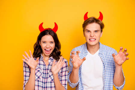 Close up photo of pair in love he him his she her lady boy ready for halloween party put red horns on head playing devils wearing casual plaid shirts outfit isolated on yellow background 写真素材