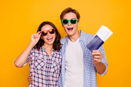 Close up photo of pair in love in summer specs he him his she her lady boy ready for trip flight going abroad have all they need wearing casual plaid shirts outfit isolated on yellow background
