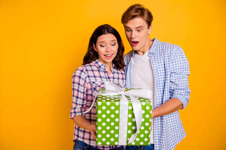 Close up photo of pair hugging he him his she her lady boy surprised took first party present shocked wearing casual plaid shirts outfit isolated on yellow background