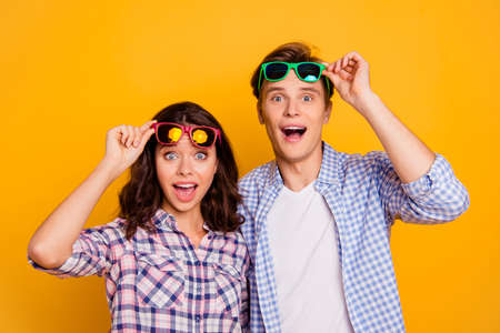 Close up photo of pair in raised up summer specs he him his she her lady boy did not expect free flight on travel open mouth wearing casual plaid shirts outfit isolated on yellow background Stock fotó