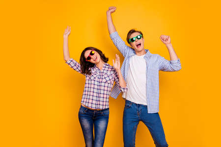 Close up photo of pair in summer specs he him his she her lady boy hands up dancing yelling cheer great bit luck wearing casual plaid shirts outfit isolated on yellow background 스톡 콘텐츠