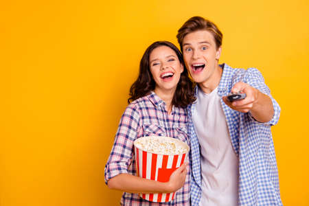 Close up photo of pair delighted from gladness he him his she her lady guy choosing channel for watching movie wearing casual plaid shirts outfit isolated on yellow background