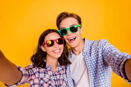 Close up photo of pair in love he him his she her lady boy after wedding going to honeymoon take make first photos wearing casual plaid shirt outfit isolated on yellow background