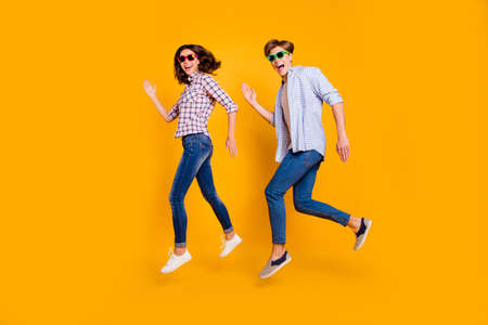 Close up full length body size photo of pair in summer specs he him his she her lady boy make dance moves jumping high fooling around wearing casual plaid shirt outfit isolated on yellow background