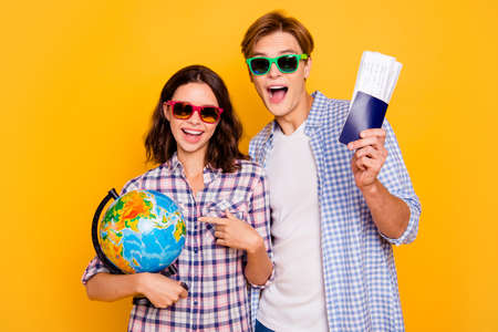 Close up photo of pair  love in summer specs he him his she her lady boy with globe and tickets in hands glad to pick australia for trip wearing casual plaid shirt outfit isolated on yellow background