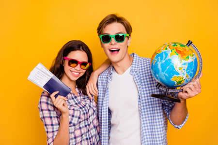 Close up photo of pair in love in summer specs he him his she her lady boy with globe and tickets in hands packed ready for adventures wearing casual plaid shirt outfit isolated on yellow background