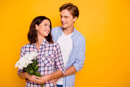 Close up photo of pair in love he him his she her lady boy bring flowers holding each other in hugs romance moment wearing casual plaid shirt outfit isolated on yellow background