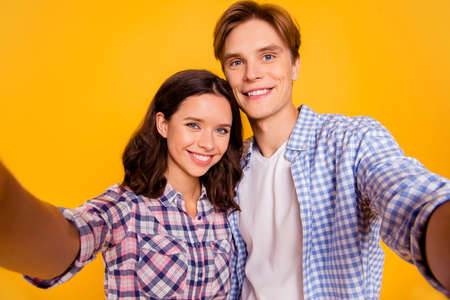 Close up photo of pair in love he him his she her lady boy telling relatives on web camera skype news about engagement   wearing casual plaid shirt outfit isolated on yellow background