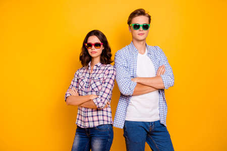 Close up photo of pair in summer specs he him his she her lady boy hands crossed standing back to back self-confident examiners wearing casual plaid shirts outfit isolated on yellow background