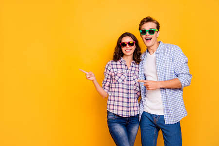 Close up photo of pair in summer specs he him his she her lady boy hands show to empty space on news wearing casual denim jeans plaid shirts outfit isolated on yellow background Foto de archivo