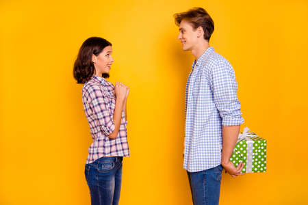 Close up photo of pair in love he him his she her lady boy glad to give present to dear girl expecting wondered what in behind back wearing casual plaid shirts outfit isolated on yellow background Foto de archivo - 122604915