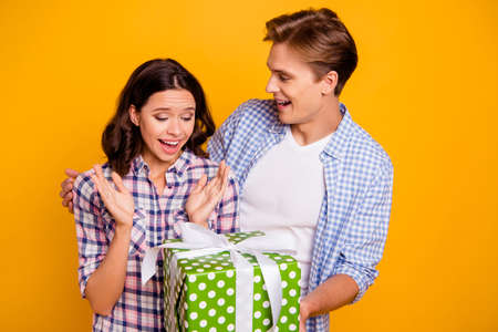 Close up photo of pair in love he him his she her lady boy husband making surprise for wife large giftbox wearing casual plaid shirts outfit isolated on yellow background