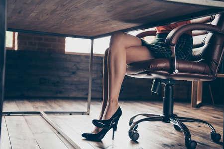 Przycięty widok zdjęcie uroczych atrakcyjnych nóg surowa poważna dama siedzieć biurko skórzane krzesło rozwiązać problem firmy wspaniały wspaniały wspaniały elegancki kraciasty spódnica czerwony sweter wnętrze