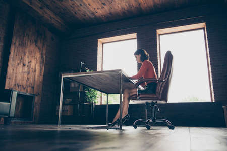 Profile side low angle view of her she attractive busy experienced executive company founder ceo boss chief creative designer sitting in chair loft brick industrial style interior work place station