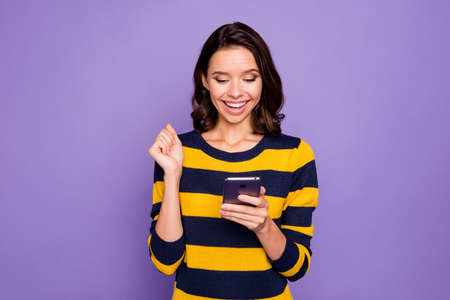 Close up photo beautiful amazing she her lady hands hold telephone reader news information amazed excited big surprise shock omg wow wear blue yellow striped pullover isolated violet purple background