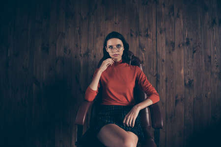 Portrait clever magnificent attractive entrepreneur sit leather furniture touch chin hand finger contemplate think thoughtful trendy stylish style red sweater plaid skirt brunette eyewear industrial