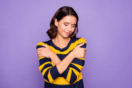 Close up photo beautiful amazing she her lady arms hands hold pleasant clothes jumper eyes closed overjoyed impressed wear blue yellow striped pullover isolated violet purple background