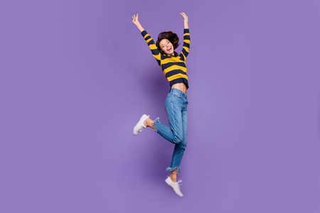 Full length body size side profile photo beautiful she her lady hands arms raised yell scream shout jump high flight playful mood wear blue yellow striped pullover isolated violet purple background 写真素材