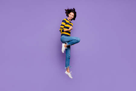 Full length body size side profile photo beautiful she her lady hands arms fists air yell scream shout jump high flight playful mood wear blue yellow striped pullover isolated violet purple background
