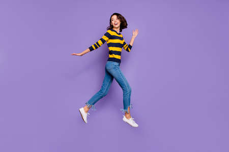 Full length side profile body size photo beautiful she her lady cheerful jump high flight hurry shopping sale discount mall store wear blue yellow striped pullover isolated violet purple background 写真素材 - 122697864