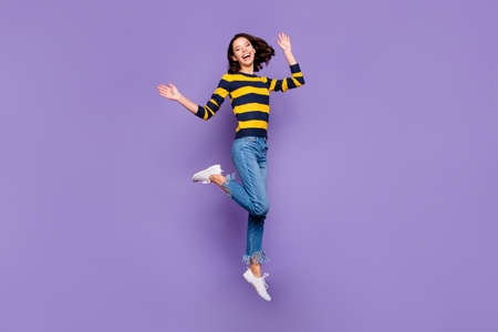 Full length body size side profile photo beautiful amazing she her lady excited jump high flight party person people energetic wear blue yellow striped pullover isolated violet purple background