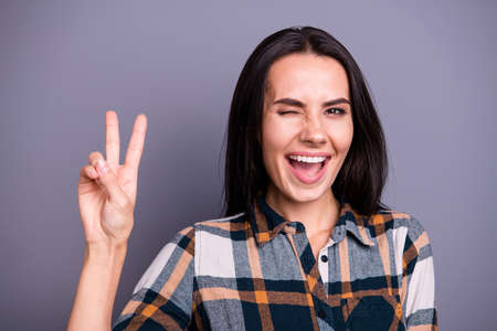 Close-up portrait of her she nice lovely pretty winsome attractive cheerful cheery positive straight-haired lady wearing checked plaid showing v-sign isolated over gray pastel background