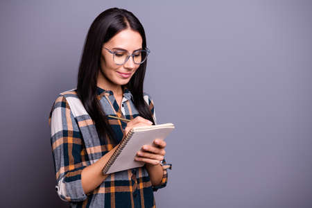 Portrait of attractive charming cute youth people thoughtful take notes prepare report wear specs dressed stylish trendy checked shirt isolated grey background Stock Photo