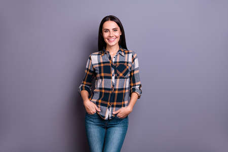 Portrait content attractive youngster people education learning person long haircut hairdo dressed checked outfit jeans place hands palms pockets modern glad excited isolated grey background Foto de archivo