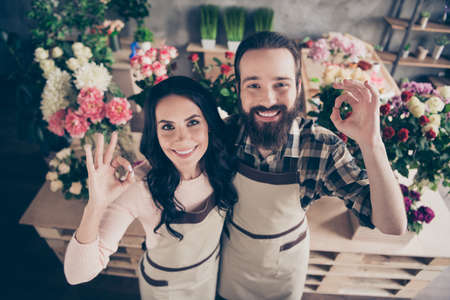 Close up top above high angle photo two people she her wife lady him his he husband guy advice buy buyer fingers okey symbol compositions bunches fresh flowers owners small flower shop room indoors