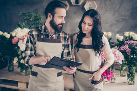Close up side profile photo two people she her lady him his he guy excited earn order money show numbers kinds compositions bunches fresh flowers owners wear aprons small flower shop room indoors